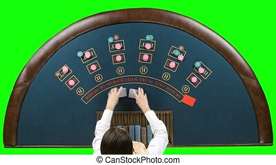 Dealer handling playing cards at a poker table. Green screen
