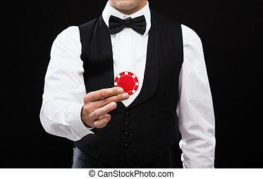 dealer holding red poker chip