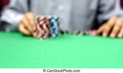 dealer moves a stack of poker chips, close up