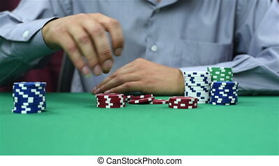 dealer recounts poker chips, close up