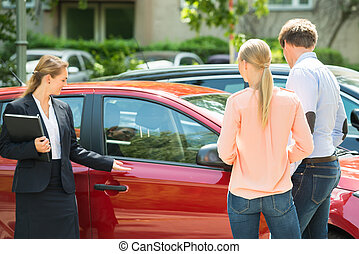 Dealer Showing Car To Couple