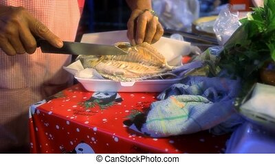 dealer shows grilled Tilapia fish inside the willingness in street market of Thailand