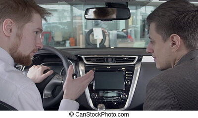 Dealer tells customer about advantages of new model of car in showroom inside. slow motion.