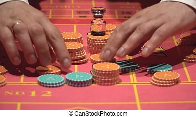 Dealer working , placing bets, collect chips for roulette in casino.