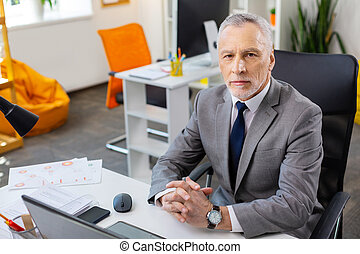 Grey-haired strict man in grey costume being concentrated at work