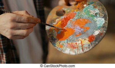 Dealing with Paint on Palette - Male artist dealing with...