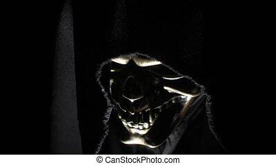 Death in the hood in the dark - Man in a skeleton mask in ...