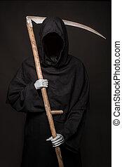 Death with scythe standing in the dark. Halloween. Studio...