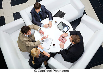 Debate - Portrait of businesspeople sitting around at the...