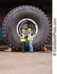 debout, énorme, pneu, ouvriers, devant, entrepôt