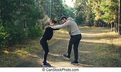 debout, épaules, femme, autour de, joints, chaque, parc, arbres verts, sports, apprécier, jambes, en mouvement, ils., tenue, warming-up, sentier, autre, homme