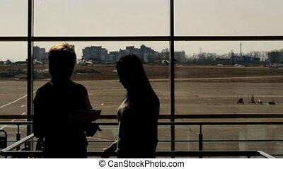 debout, aéroport, deux, conversation, attente, salle, femmes