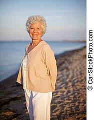 debout, aîné, femme, seul, plage