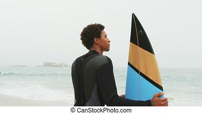 debout, africaine, vue, arrière, mâle, surfeur, américain, 4k, planche surf, plage