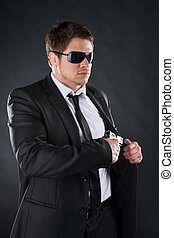 debout, bodyguard., loin, jeune, formalwear, fusil, regarder, confiant, quoique, noir, contre, fond, tenue, homme, lunettes