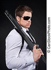 debout, bodyguard., loin, vue, jeune, contre, fusil, regarder, confiant, quoique, arrière-plan noir, tenue, cravate, homme, côté, chemise