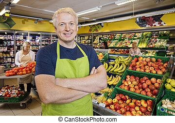 debout, bras croisés, fruits, vendeur, magasin