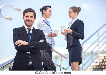 debout, business, escaliers., gens, jeune, trois, regarder, appareil photo, closeup, homme souriant
