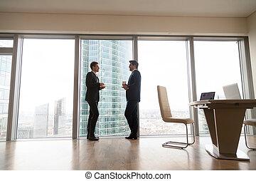 debout, café, bureau, deux, fenêtre, hommes affaires, plein-longueur