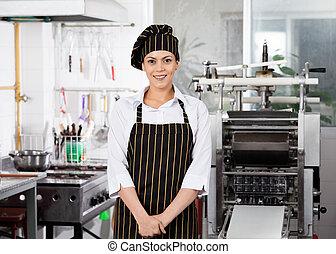 debout, chef cuistot, sourire, femme, cuisine