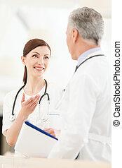 debout, collègue, consultant, femme, elle, docteur, jeune, mûrir, devant, sourire, faire gestes, colleague.