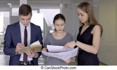 debout, collègues, documents, bureau., moderne, jeune, discuter