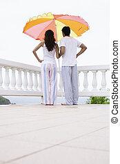 debout, couple, jeune regarder, sous, parasol, vue