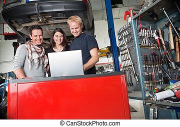 debout, couple, mécanicien, utilisation, sourire, ordinateur portable