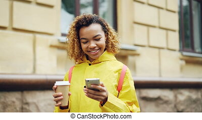 debout, course, café, femme, regarder, loin, moderne, mélangé, surfer, regarder, photos, ou, smartphone, prendre, tenue, filet, écran, utilisation, outdoors., sourire, séduisant