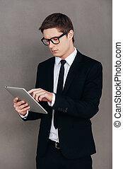 debout, examiner, sien, tablette, fonctionnement, tablet., jeune, formalwear, gris, confiant, quoique, contre, fond, numérique, nouvel homme
