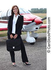 debout, femme affaires, avion, heureux, devant