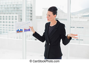debout, femme affaires, clair, bureau, graphiques