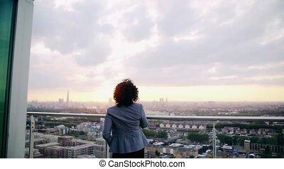debout, femme affaires, terrasse, sunset., vue postérieure