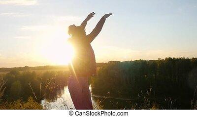 debout, femme, autour de, elle, soleil, sauts, rocher, mouvement, rotation, lent, par, mûrir, mains, pendant, ascensions, joyeux, sunset.