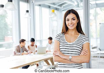 debout, femme, bureau, bras croisés, heureux