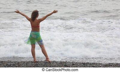 debout, femme, jeune, contre, mer, vagues, plage caillou