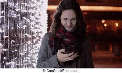 debout, femme, lumières, jeune, neige, téléphone, séduisant, nuit, conversation, tomber, mur, noël