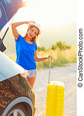 debout, femme, tronc voiture, jaune, valise, garé, bord route
