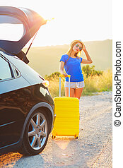 debout, femme, tronc voiture, jeune, jaune, valise
