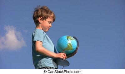 debout, garçon, globe, tourne, terrestre