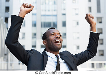 debout, garder, business, positivité, africaine, jeune, winner., bras, quoique, formalwear, exprimer, dehors, élevé, homme, heureux