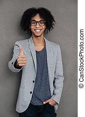 debout, grand, sien, pouce haut, projection, gris, contre, jeune, gai, quoique, fond, africaine, sourire, job!, homme