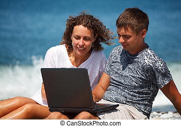 debout, gros plan, knees., séance, ordinateur portable, regarder, leur, seashore., intérêt, girl, homme