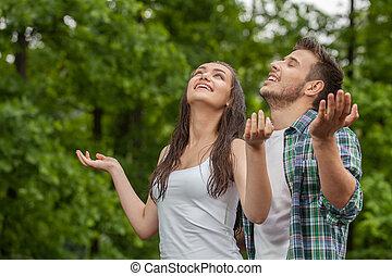 debout, heureux, élevé, femme, jeune, pluie, bras, sous, apprécier, summer., homme