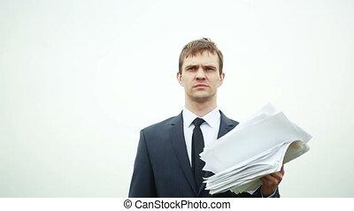 debout, homme affaires, papier, wind., pile