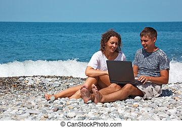 debout, knees., séance, ordinateur portable, regarder, leur, seashore., intérêt, girl, homme