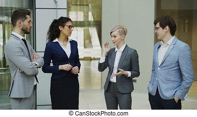debout, lobby., collègues, groupe, bureau, elle, gens, femme affaires, affaire, business, conversation, quoique, avenir, discuter