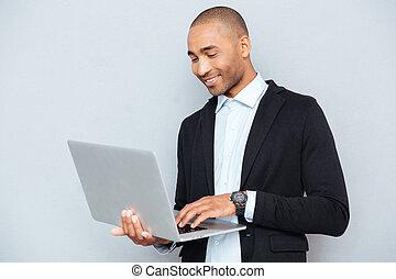 debout, ordinateur portable, jeune, américain, africaine, utilisation, homme souriant
