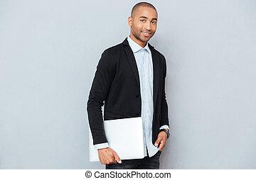 debout, ordinateur portable, jeune, américain, tenue, homme africain, beau