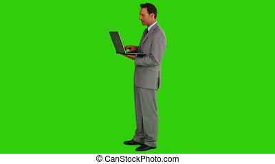debout, ordinateur portable, sien, regarder, appareil photo, homme affaires